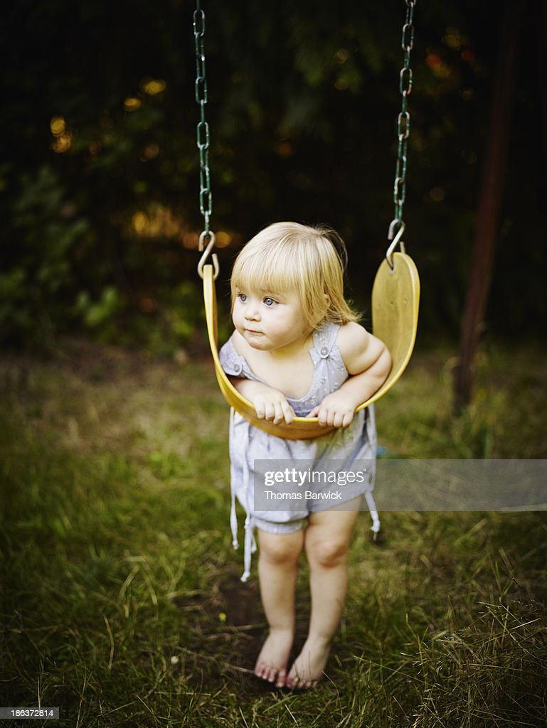 Young toddler leaning on swing : Stock Photo