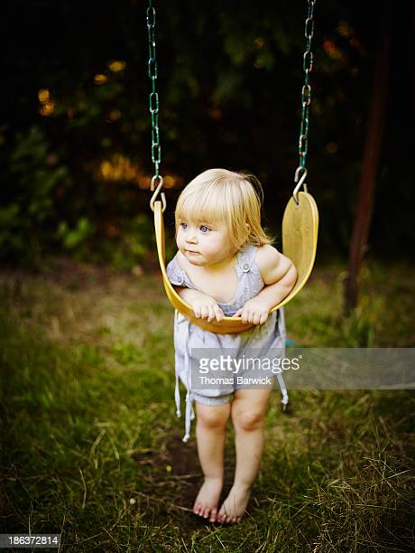 Young toddler leaning on swing