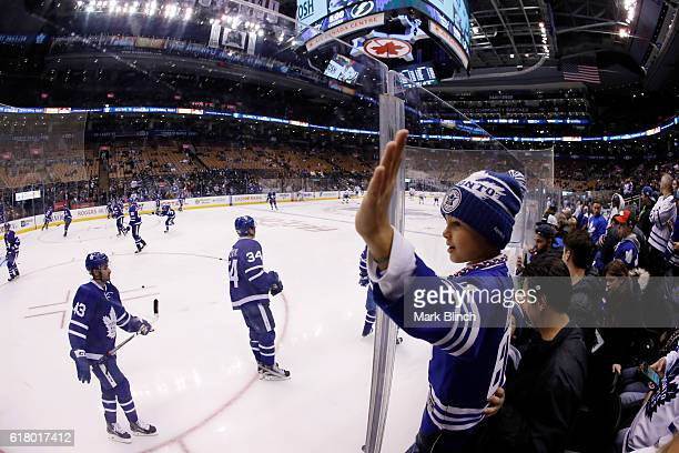 A young Toronto Maple Leafs fan watches the team skate during warmup before the Leafs take on the Tampa Bay Lightning at the Air Canada Centre on...