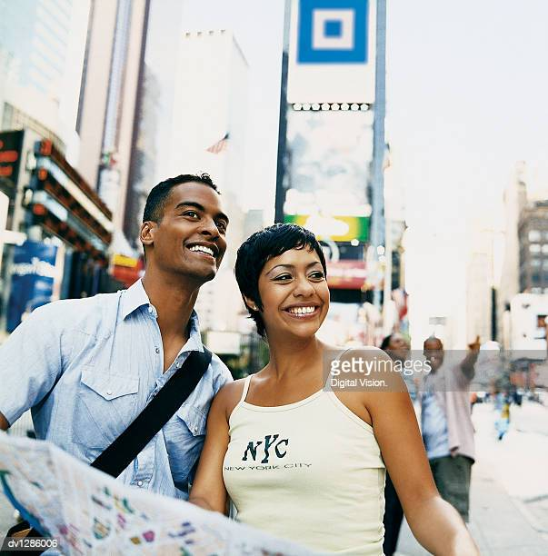 Young Tourist Couple in a New York Street Holding a Map