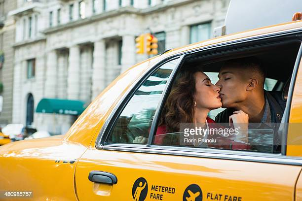 Young tourist couple kissing in yellow cab, New York City, USA