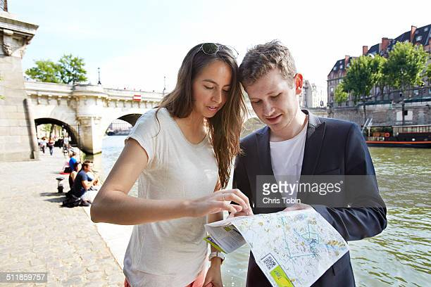 Young tourist couple looking at map in Paris