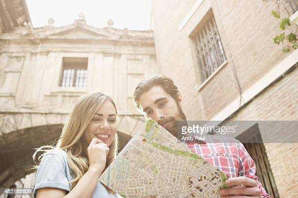 Young tourist couple looking at map outside Valencia Cathedral, Valencia, Spain