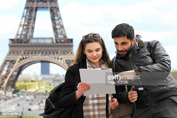 Jeune couple de touristes regardant carte