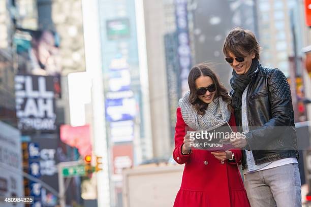 Young tourist couple looking at newspaper, New York City, USA