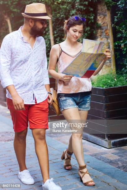 Young tourist couple walking around with map