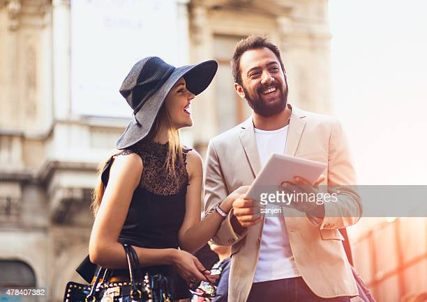 Young tourist couple with digital tablet on the street