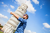 Young tourist having fun in Pisa close to the leaning tower.