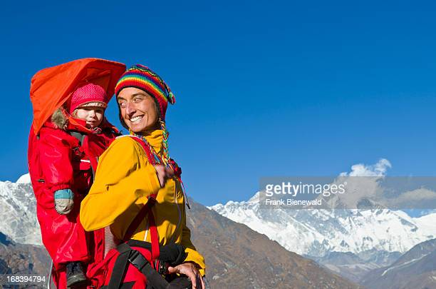 A young tourist mother carrying her little child in a child carrier rucksack on her back trekking towards Mount Everest Mountain above Namche Bazar...
