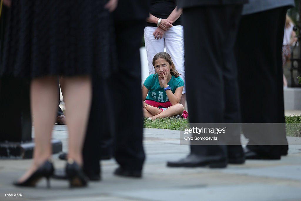 A young tourist sits in the grass as she listens to Republican members of the House of Representatives hold a brief news conference outside the U.S. Capitol August 2, 2013 in Washington, DC. With Congress heading into its summer recess, the representatives held the news conference to 'highlight House Republicans' efforts to stop government abuse and restrain a runaway government.'