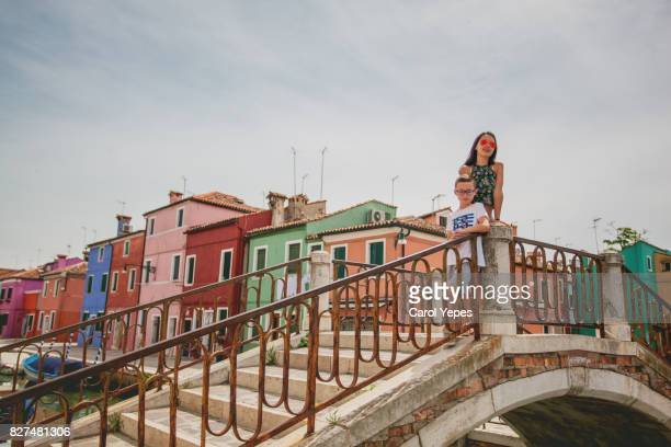 young tourist standing in front of Burano colorful Buildings