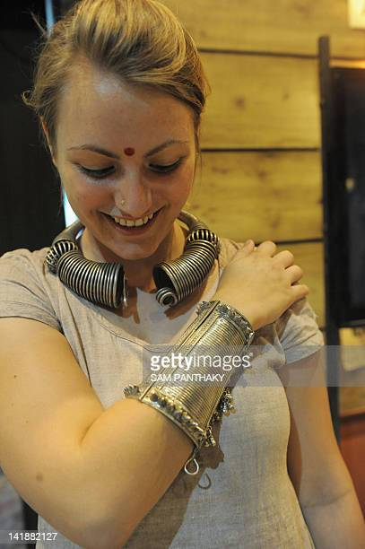 A young tourist tries on silver ornaments from Gujarat's remote Kutch region on the second day of 'Craftroots Festival 2012' at The Rajpath Club in...