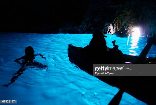 A young Tourist Woman is swimming in the amazing Blue Waters in the Cave of the Blue Grotto at the Island of Capri on June 24 2015 in Naples Italy