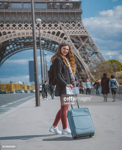 Young tourist woman walking with suitcase