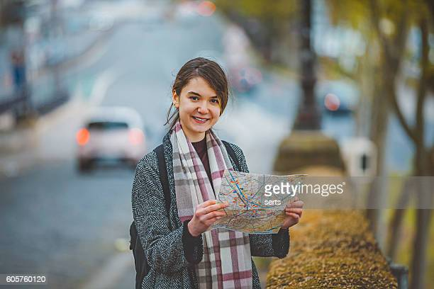 Young tourist woman with city map