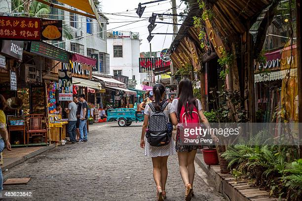 Young tourists walking on the narrow street in Zeng Cuo An Zeng Cuo An formerly a small fishing village located in Xiamen Siming District now is a...