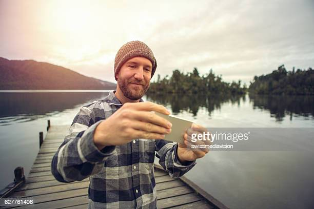 Young travel man takes selfie portrait on wooden pier
