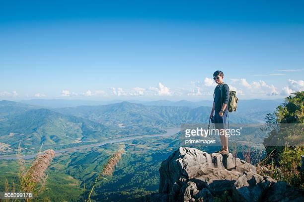 Jeune voyageur debout sur les montagnes se tourne vers le coucher du soleil.