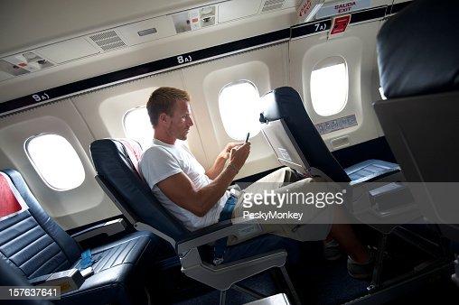 Young viaje hombre sentado enviando mensajes de texto de asiento de avión