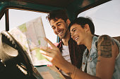 Close up of cheerful couple looking at a map sitting in car. Smiling man and woman using map to navigate on a road trip.