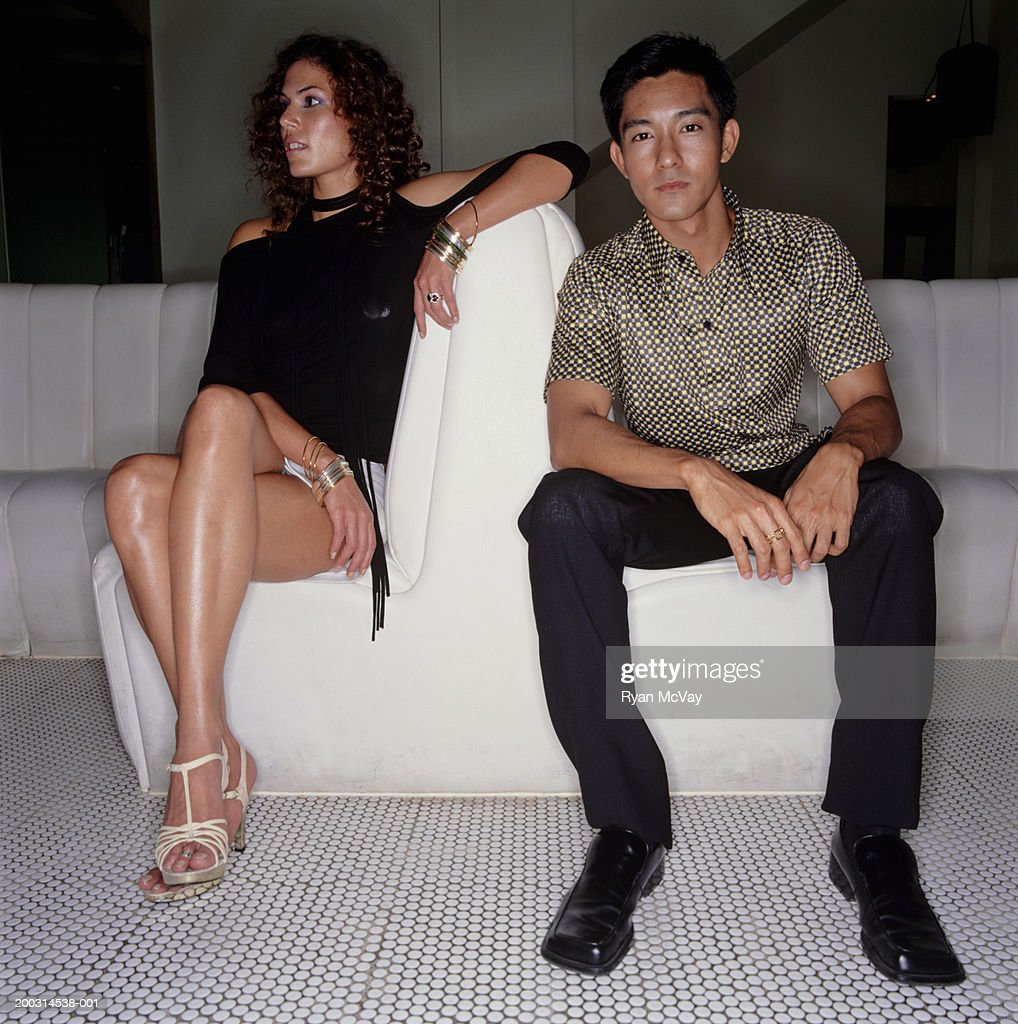 Young trendy couple sitting in night club : Stock Photo