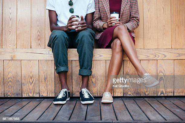 Young trendy ethnic African couple sitting on bench outside coffee shop in trendy street in Braamfontein Johannesburg South Africa