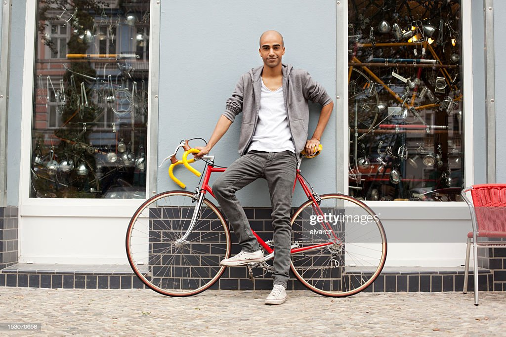 Young trendy guy with a bicycle : Stock Photo