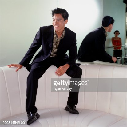 Young trendy man sitting on couch in club smiling at young woman : Stock Photo