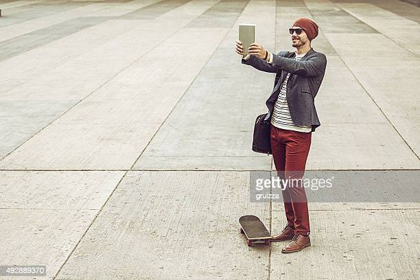 Tendance jeune homme prenant selfie photo avec tablette numérique