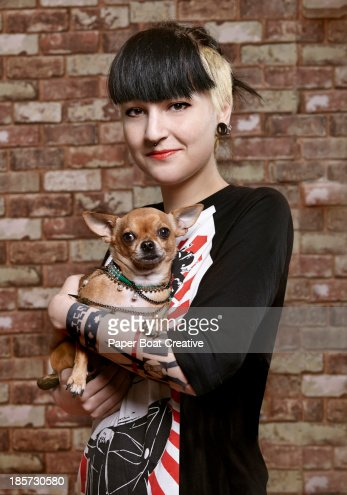 Young trendy student holding her pet dog : Stock Photo