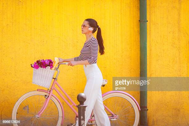 Young trendy woman pushes the pink bicycle beside the yellow wall