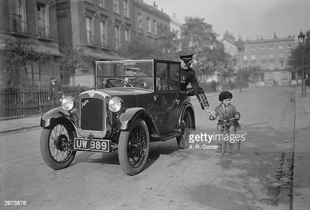 A young tricyclist gets a helping hand from the passenger of an Austin Seven motor car Mr High Test of Pratt's Motor Spirit on his way to the Olympia...