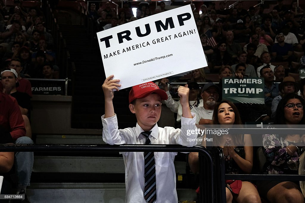A young Trump supporter holds a sign as the Presumptive pepublican presidential candidate speaks at a rally in Fresno on May 27, 2016 in Fresno, California. Trump is on a Western campaign trip which saw stops in North Dakota and Montana yesterday and two more in California today.