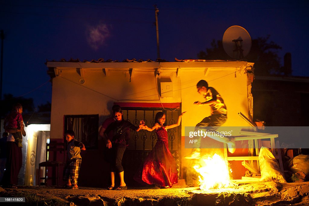 A young Turkish gypsy stand jumps over a fire during the celebration of the annual Spring Festival 'Hidirellez', on May 5, 2013, 2013, in Edirne, south-western Turkey. Gypsies celebrate the beginning of the spring season according to their calendar. Hidirellez is celebrated as the day on which Prophets Hizir (Al-Khidr) and Ilyas (Elijah) met on earth.