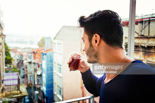 Young Turkish man drinks tea while looking down his street