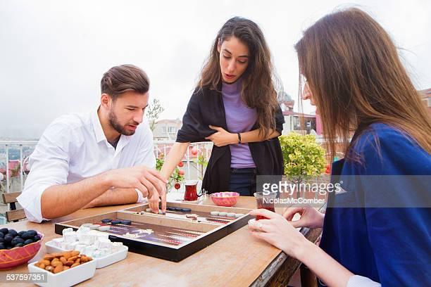Jungen türkischen Frau lehrt Freunden Spielregeln tavla