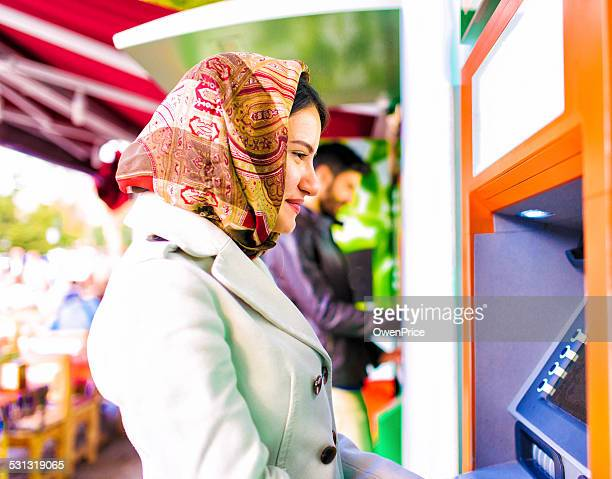 Young Turkish woman using ATM in Istanbul