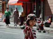 A young Uighur girl waits near the main bazaar in the Muslim quarter of Urumqi Xinjiang Province on June 29 2013 China's staterun media on June 29...