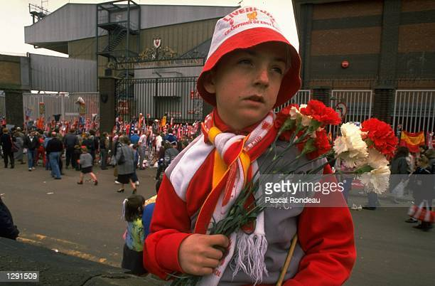 A young unhappy Liverpool supporter carries some flowers in his team's colours to lay in tribute after the Hillsborough disaster at Anfield in...