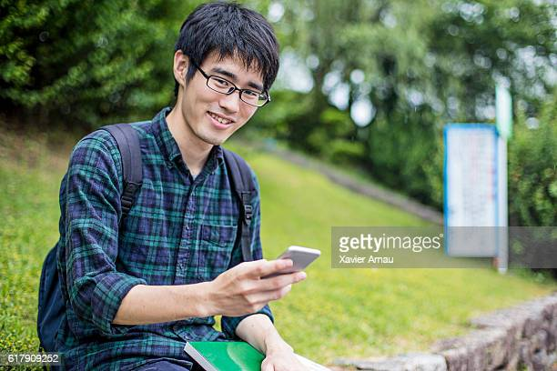 Young university student with mobile phone outdoors