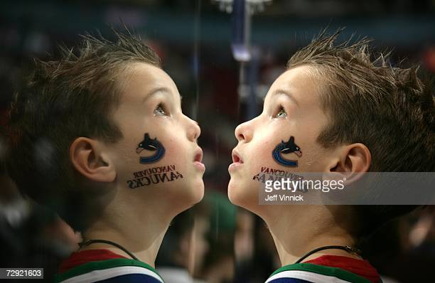 A young Vancouver Canuck fan's face is reflected in the glass as he watches a replay during a game between the Canucks and the Dallas Stars at...