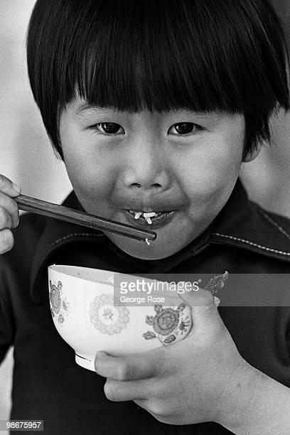 A young Vietnamese boy enjoys a bowl of rice as seen in this 1975 Camp Pendleton Oceanside California photo