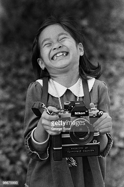 A young Vietnamese girl plays with a photographer's camera as seen in this 1975 Camp Pendleton Oceanside California photo