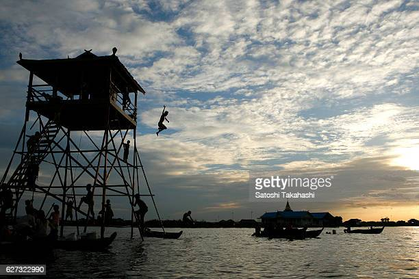 A young Vietnamese jumping into Tonle Sap lake in kompong Luong floating village