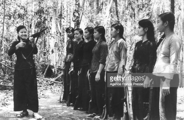 A young Vietnamese woman demonstrates the use of a rifle to a group of teenage girls in a jungle clearing training to fight in the Viet Cong war...