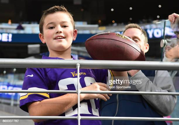 A young Vikings fan displays the ball thrown to him by Minnesota Vikings running back Jerick McKinnon during a NFL game between the Minnesota Vikings...