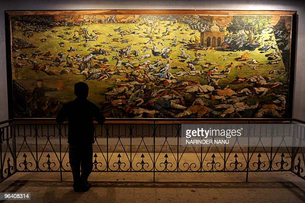 A young visitor looks at a painting depicting the Amritsar Massare at Jallianwala Bagh in Amritsar on February 4 2010 The Amritsar Massacre also...
