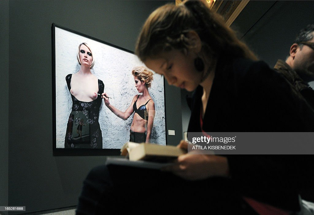 A young visitor reads her book in front of a picture by the German born photographer Helmut Newton (Neustadter) (1920-2004) in the Museum of Fine Arts of Budapest on April 2, 2013 during a presentation of Newton's photographic exhibition for press. The show features around 250 shots by one of the greatest figures of fashion and advertising photography Newton, reflecting his most significant creative periods. The material will be assembled with the cooperation of the Helmut Newton Stiftung, the foundation taking care of the artist's oeuvre in Berlin. The photographic exhibition will be opened on April 3. AFP PHOTO / ATTILA KISBENEDEK CLIENTS