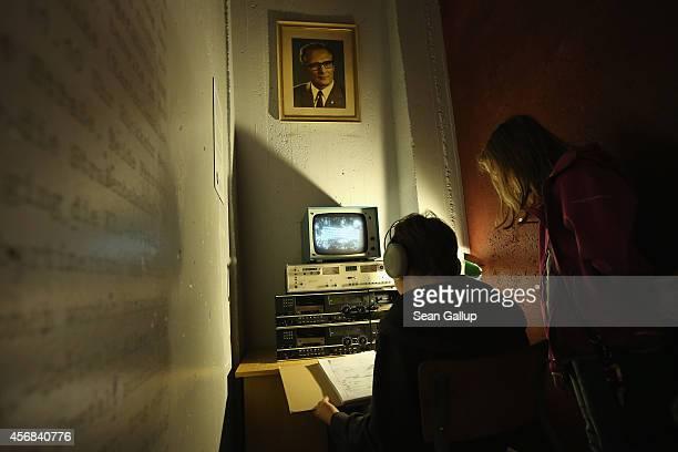 Young visitors look at a reconstructed Stasi secret police surveillance corner under a portrait of former East German communist leader Erich Honecker...