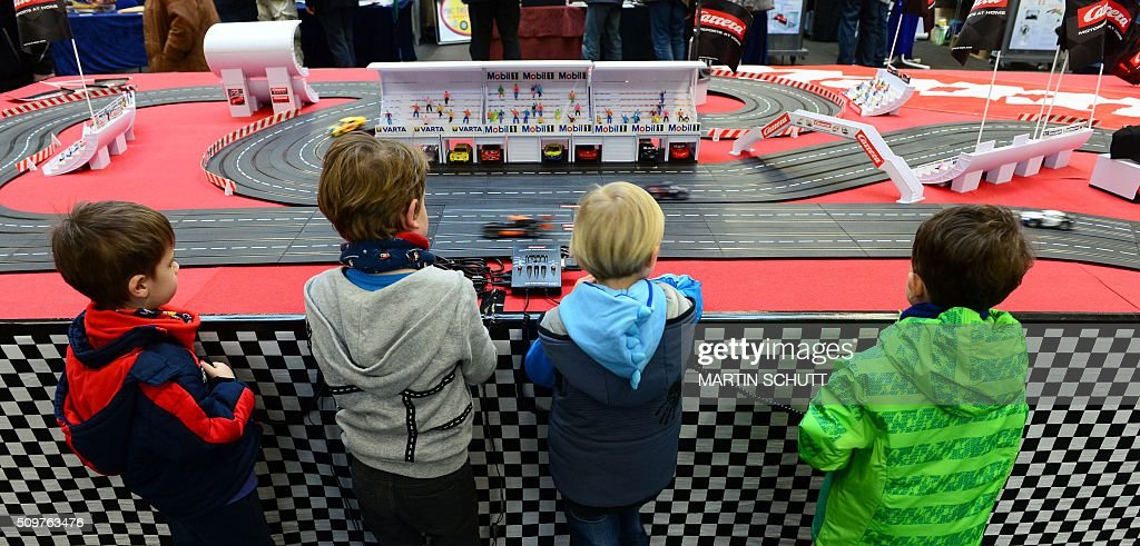 Young visitors look at Carrera toy race track on display at the 'Erlebniswelt Modellbau' model making fair on February 12, 2016 in Erfurt, eastern Germany. The fair is running until February 14, 2016. / AFP / dpa / Martin Schutt / Germany OUT
